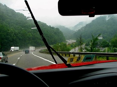 A view from inside a car driving down a rainy road, with the windshield wipers swiping across the glass.