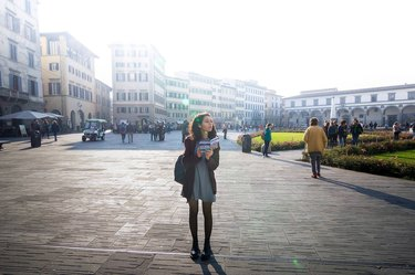 Young woman tourist holding guidebook in Italian plaza