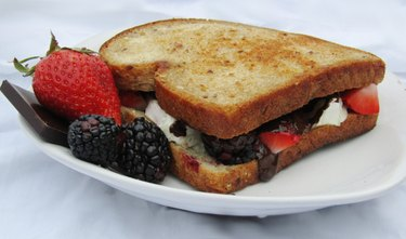 A white plate with a sandwich, and chocolate and blackberries on the side.