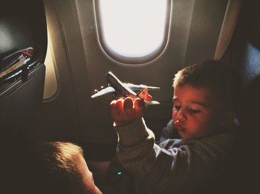 Toddler in airplane seat playing with toy airplane