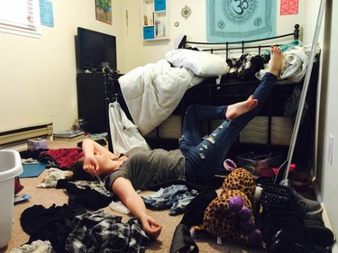College student amid messy dorm room