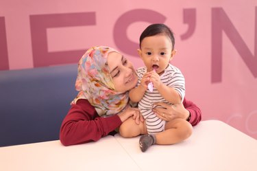 Young hijabi mother with young child in a pink office