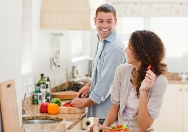 couple laughing and making dinner