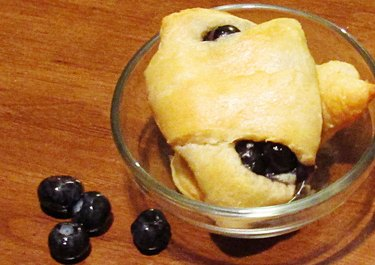 Baked crescent roll stuffed with blueberries and cream cheese, in the background there are scattered blueberries.