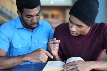 Two young Black men discussing an open book