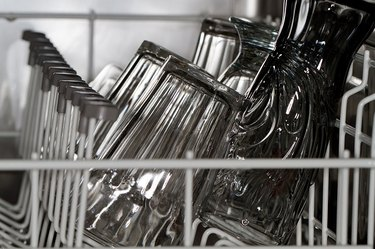 A close-up of drinking glasses stacked inside the rack of a dishwasher.