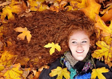 Redheaded woman lying in autumn leaves