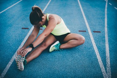 Young woman stretching on a blue track