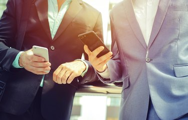 Two men in business suits looking at phones