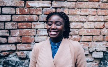 Young Black woman smiling in front of brick wall