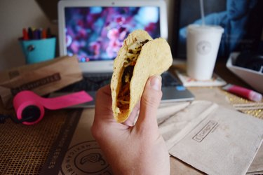 POV shot holding taco in front of laptop