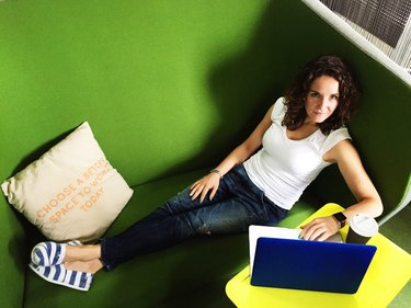 Woman lying on green couch while working on laptop