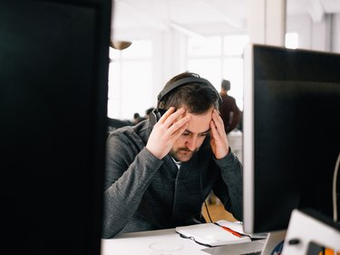 Bearded man at computer station looking stressed