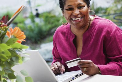 Middle-aged African woman with credit card and laptop outdoors