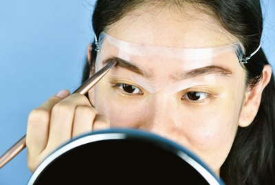 Asian woman applying cosmetics makeup, Eyebrows template head strap use for shaping perfect brows