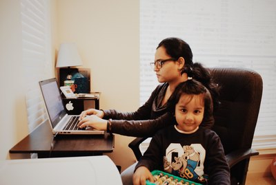 Working mom busy 'work from home' while kid plays around happily