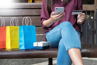 Woman paying with credit card on phone with gift bags next to her
