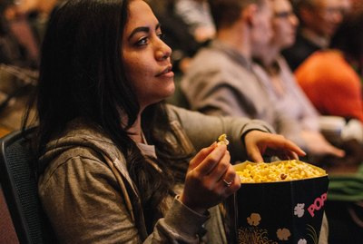 Woman in movie theater holding large bag of popcorn