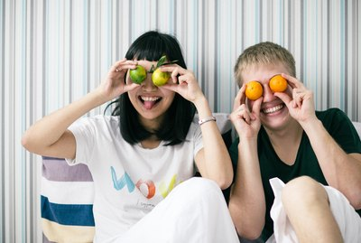 Cute interracial couple holding citrus fruit over eyes