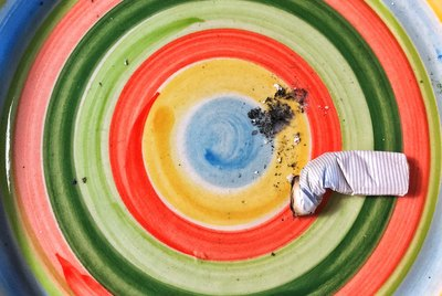 Colorful bowl with stubbed cigarette