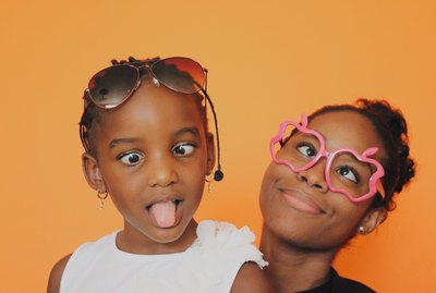 Young Black girl and female relative making funny faces together