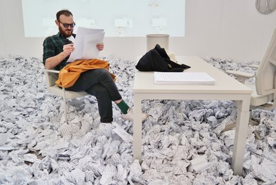 Man reading in office surrounded by crumpled up paper