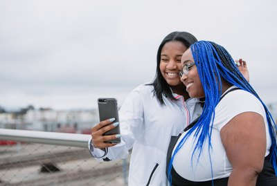 Mother and daughter family taking a selfie with a mobile smart phone device