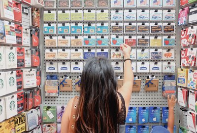 A young millennial woman shopping for the right gift card gift at the store