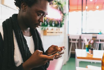 Young Black man looking at phone in cafe