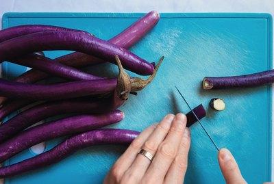 Closeup of hands dicing eggplants