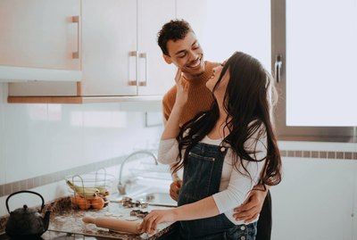 Pregnant couple being cute in a kitchen