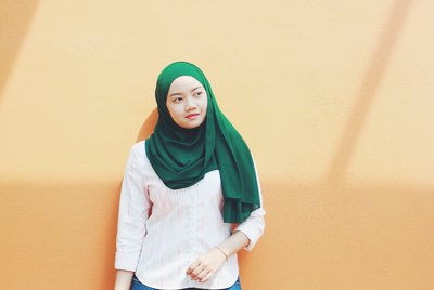 Young Asian hijabi standing against peach-colored wall