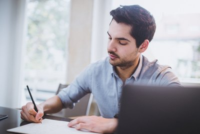 Young man is taking handwritten notes on paper at his desk