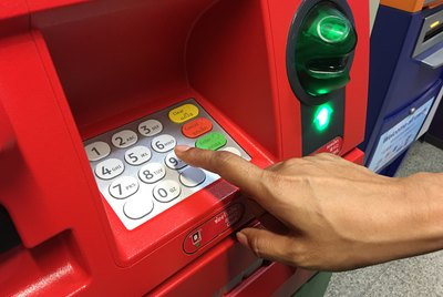 Woman's hand typing on ATM keypad