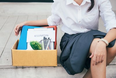 "Young woman sitting on curb with box of desk items, including letter reading ""Resignation"""