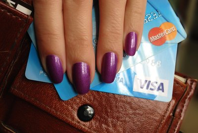 Manicured hand holding credit cards