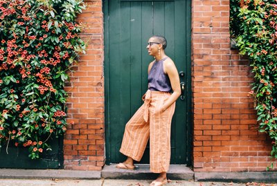 Young relaxed Black woman posing in front of old door outside