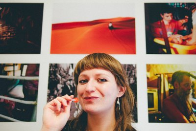 Smiling woman with lollipop in front of photo gallery