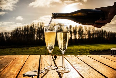 Hand pouring champagne into two flutes outdoors