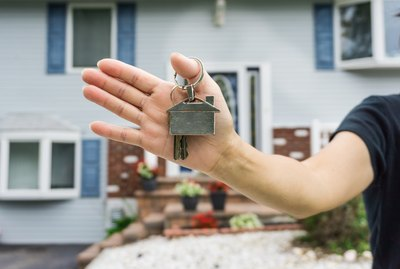 Real estate agent holding new house key in front of house