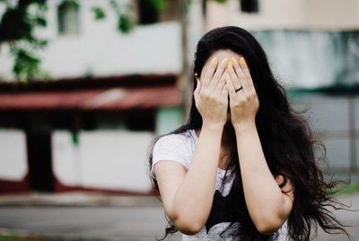 Young woman with long black hair and yellow nail polish hiding her face in her hands