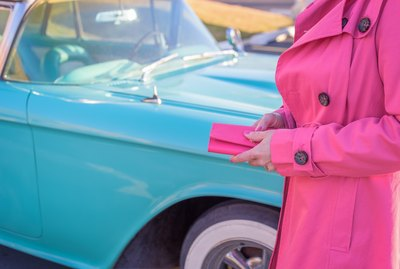 Woman in hot pink coat holding wallet looking to buy classic baby blue retro car