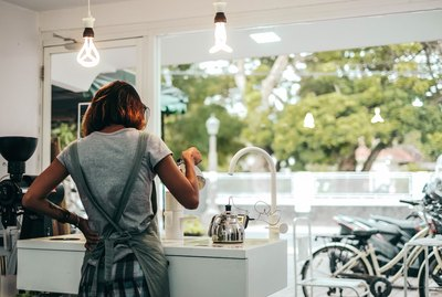 Barista at sunlit coffee shop from behind
