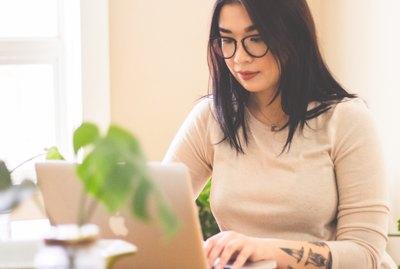 Tattooed woman working on laptop