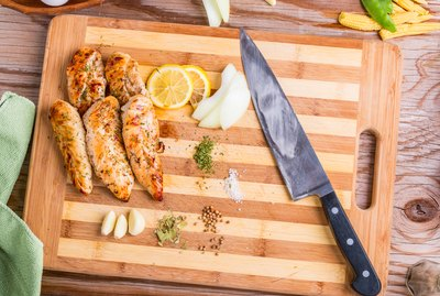 Grilled barbecue chicken breast on a bamboo cutting board on a wooden old table with garlic eggs and vegetables