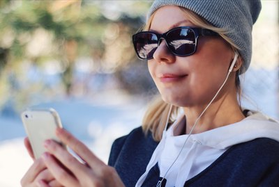 White woman listening to headphones on iPhones