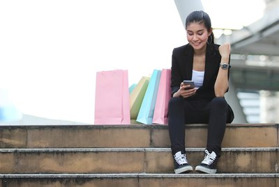 Cheerful young Asian woman looking mobile smart phone at outdoors. Shopping online concept.