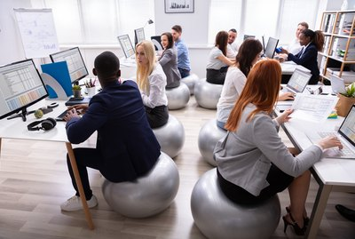 Group Of Businesspeople Discussing While Working In Office