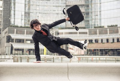 How Does Switching Jobs Affect My Wage Garnishment?Business man with suitcase jumping over urban obstacles