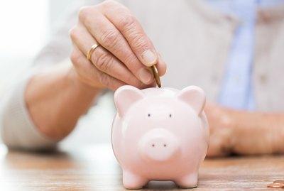 senior woman hand putting money to piggy bank